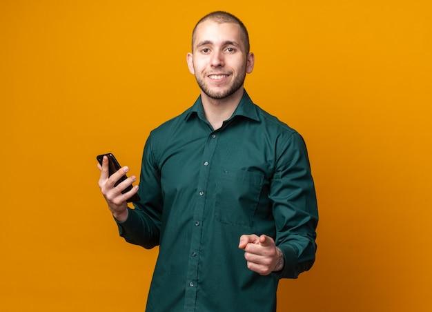 Glimlachende jonge knappe kerel die een groen overhemd draagt dat telefoon vasthoudt en naar voren wijst