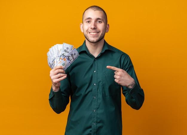 Glimlachende jonge knappe kerel die een groen overhemd draagt en naar contant geld wijst