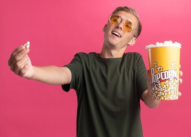 Glimlachende jonge knappe kerel die een groen overhemd en een bril draagt die popcornstuk met emmer popcorn aan voorzijde houdt die op roze muur wordt geïsoleerd
