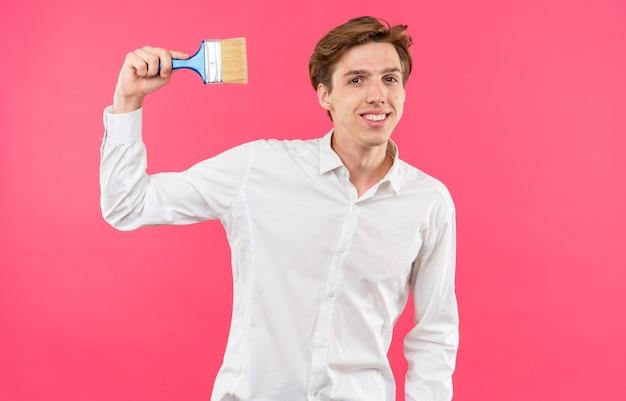 Glimlachende jonge knappe kerel die een wit overhemd draagt dat verfborstel houdt die op roze muur wordt geïsoleerd