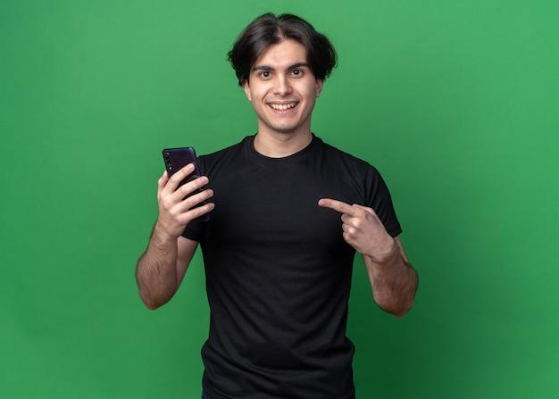 Glimlachende jonge knappe kerel die een zwart t-shirt draagt en naar de telefoon wijst die op een groene muur is geïsoleerd