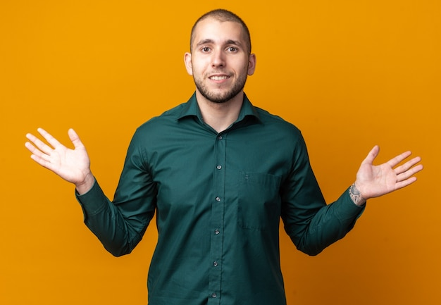 Glimlachende jonge knappe kerel die groen overhemd draagt dat handen uitspreidt