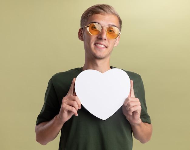 Glimlachende jonge knappe kerel die groen overhemd met glazen draagt dat de doos van de hartvorm houdt die op olijfgroene muur wordt geïsoleerd
