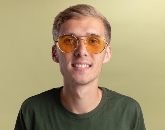 Glimlachende jonge knappe kerel die groen overhemd met glazen draagt dat op olijfgroene muur wordt geïsoleerd