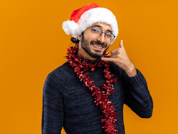 Glimlachende jonge knappe kerel die kerstmishoed met slinger op hals draagt die telefoongesprekgebaar toont dat op oranje achtergrond wordt geïsoleerd