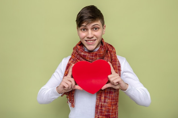 Glimlachende jonge knappe kerel die sjaal draagt die hartvormige doos houdt die op olijfgroene muur wordt geïsoleerd