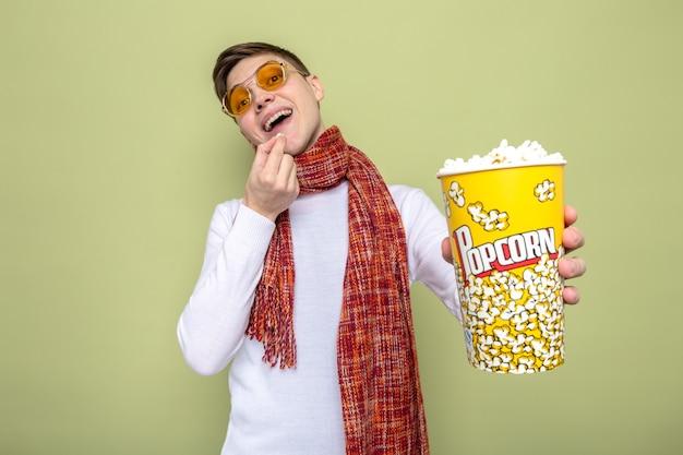 Glimlachende jonge knappe kerel die sjaal met een bril draagt die popcornemmer standhoudt