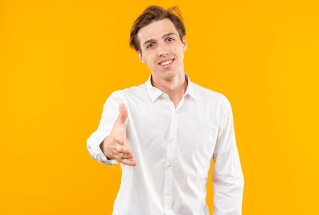 Glimlachende jonge knappe kerel die wit overhemd draagt dat hand uitsteekt bij camera die op oranje muur wordt geïsoleerd