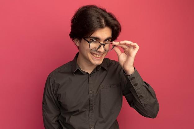 Glimlachende jonge knappe kerel die zwart t-shirt draagt dat een bril draagt en houdt die op roze muur wordt geïsoleerd