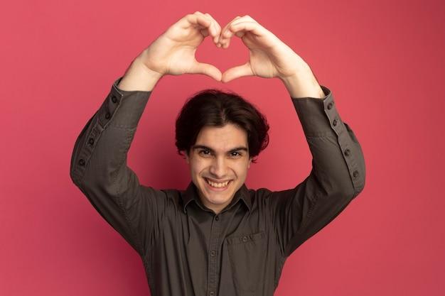 Glimlachende jonge knappe kerel die zwart t-shirt draagt dat hartgebaar toont dat op roze muur wordt geïsoleerd