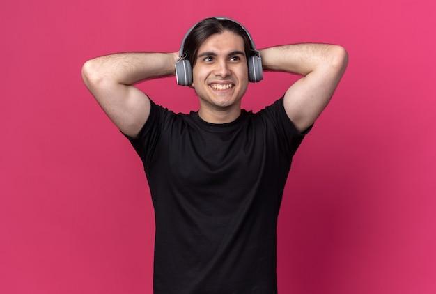 Glimlachende jonge knappe kerel die zwart t-shirt en hoofdtelefoons draagt die handen achter hoofd zetten dat op roze muur wordt geïsoleerd