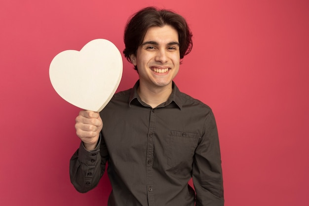 Glimlachende jonge knappe kerel die zwarte t-shirt draagt ?? die de doos van de hartvorm houdt die op roze muur wordt geïsoleerd