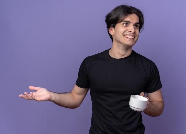 Glimlachende jonge knappe kerel die zwarte t-shirt draagt die kop van koffie houdt die hand spreidt die op purpere muur wordt geïsoleerd