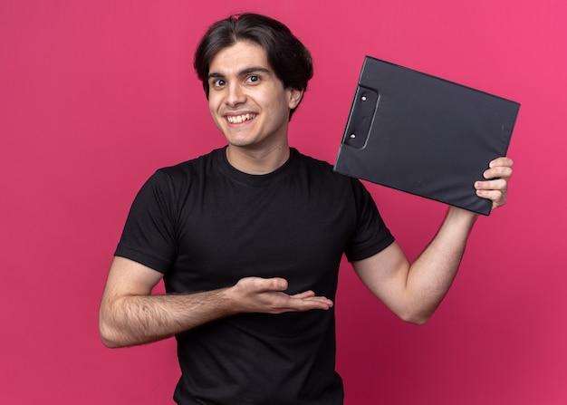 Glimlachende jonge knappe kerel die zwarte t-shirtholding draagt en naar klembord wijst dat op roze muur wordt geïsoleerd
