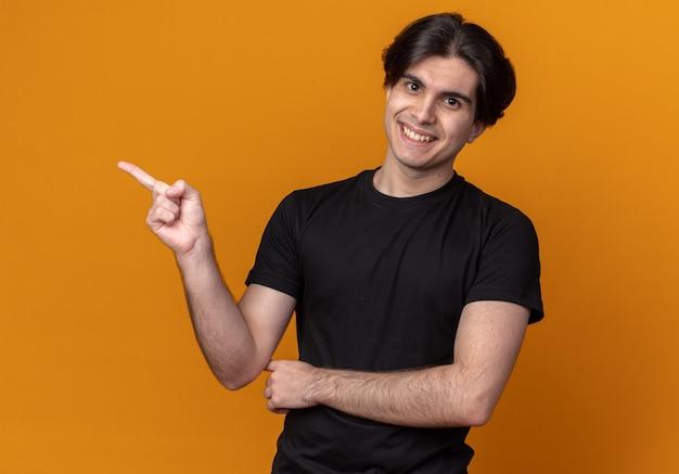 Glimlachende jonge knappe kerel die zwarte t-shirtpunten aan kant draagt die op oranje muur met exemplaarruimte worden geïsoleerd