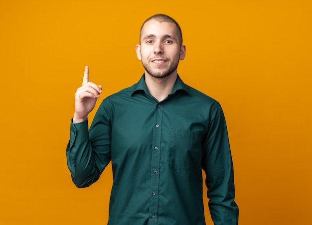 Glimlachende jonge knappe kerel met een groen shirt wijst naar boven