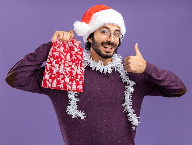 Glimlachende jonge knappe kerel met een kerstmuts met een krans op de nek die een kerstzak vasthoudt met duim omhoog geïsoleerd op een blauwe muur