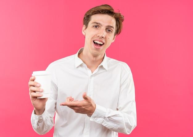 Glimlachende jonge knappe kerel met een wit overhemd in de hand en wijst met de hand naar een kopje koffie geïsoleerd op een roze muur