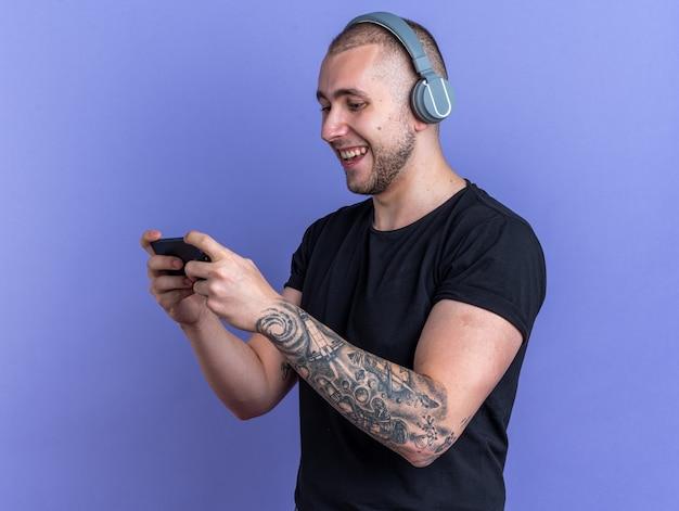 Glimlachende jonge knappe kerel met een zwart t-shirt met een koptelefoon die op de telefoon speelt geïsoleerd op een blauwe achtergrond