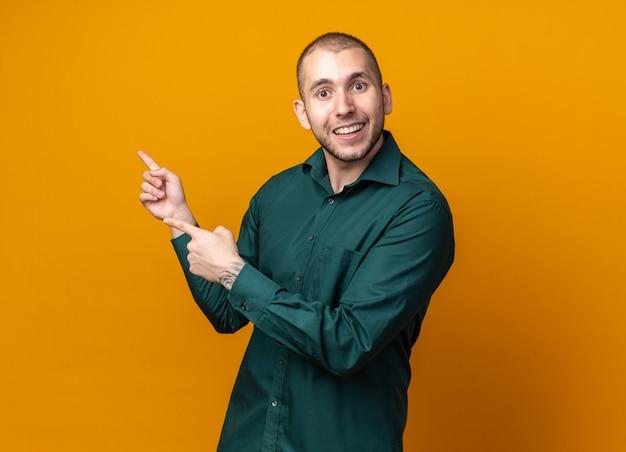 Glimlachende jonge knappe kerel met groene shirtpunten aan de zijkant