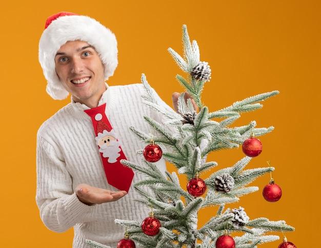 Glimlachende jonge knappe kerel met kerstmuts en stropdas van de kerstman die achter de versierde kerstboom staat en met de hand wijst naar de kerstboom die op een oranje muur is geïsoleerd
