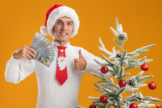 Glimlachende jonge knappe kerel met kerstmuts en stropdas van de kerstman die in de buurt van versierde kerstboom staat en geld vasthoudt en duim omhoog laat zien geïsoleerd op oranje muur