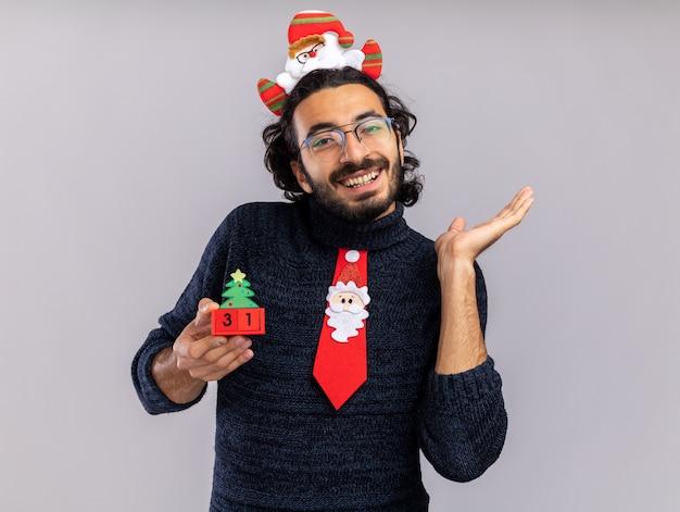 Glimlachende jonge knappe kerel met kerststropdas met haarhoepel die kerstspeelgoedpunten vasthoudt met de hand aan de zijkant geïsoleerd op een witte muur met kopieerruimte