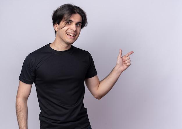 Glimlachende jonge knappe kerel met zwarte t-shirtpunten aan de zijkant geïsoleerd op een witte muur met kopieerruimte