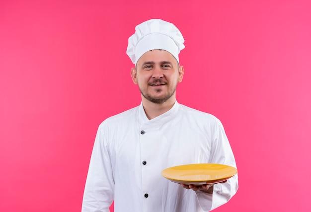 Glimlachende jonge knappe kok die in eenvormige chef-kok lege plaat houdt die op roze ruimte wordt geïsoleerd