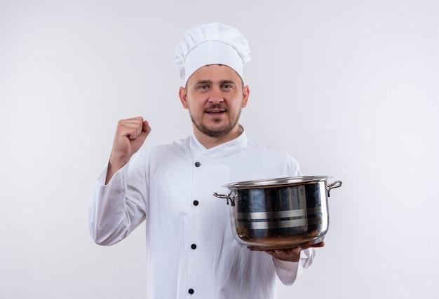 Glimlachende jonge knappe kok in de pot van de chef-kok eenvormige holding en het opheffen van vuist die op witte ruimte wordt geïsoleerd