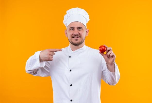 Glimlachende jonge knappe kok in eenvormige chef-kok die en op tomaat houdt die op oranje ruimte wordt geïsoleerd