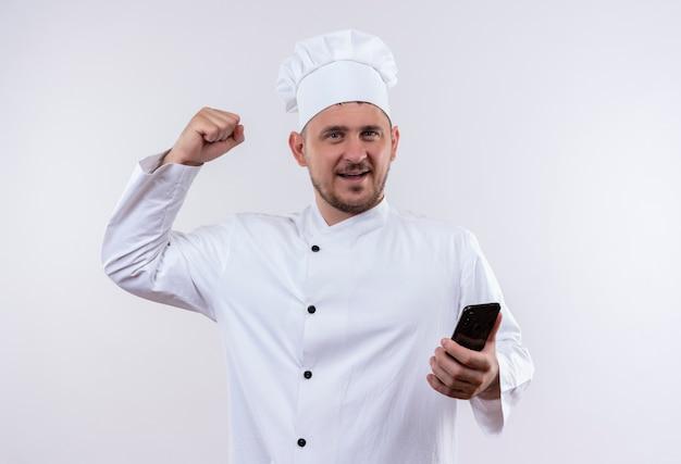 Glimlachende jonge knappe kok in eenvormige chef-kok die mobiele telefoon houdt en sterk gebaar doet dat op witte ruimte wordt geïsoleerd