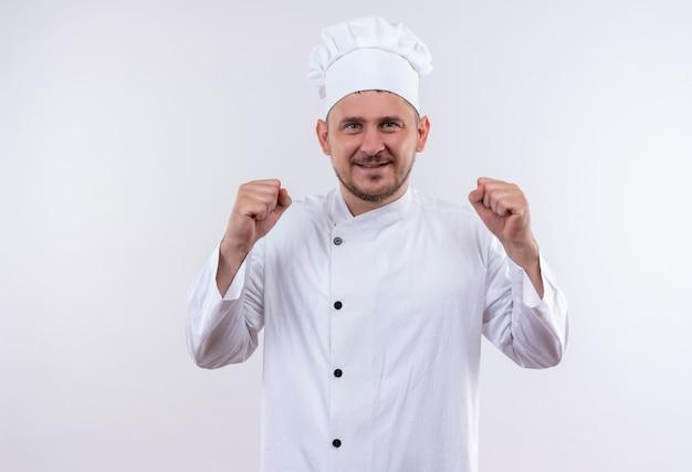 Glimlachende jonge knappe kok in eenvormige chef-kok met gebalde vuisten die op witte ruimte worden geïsoleerd