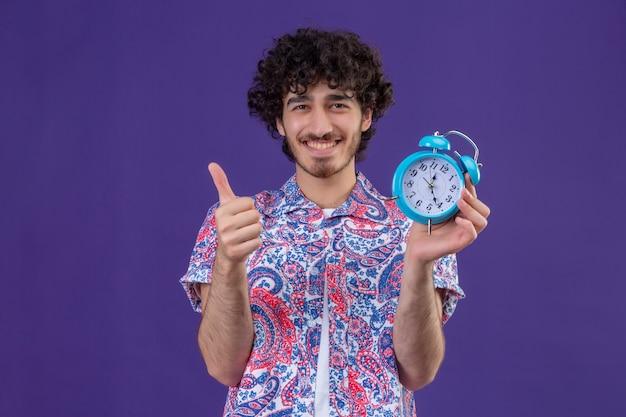 Glimlachende jonge knappe krullende de holdingswekker die van de reizigersmens duim op geïsoleerde purpere muur met exemplaarruimte toont