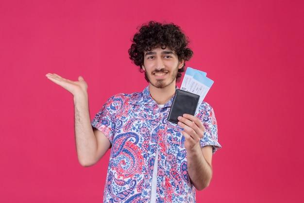 Glimlachende jonge knappe krullende reizigersmens die portefeuille en vliegtuigtickets houdt en lege hand op geïsoleerde roze muur met exemplaarruimte toont