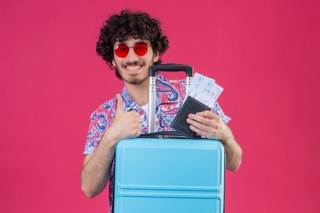 Glimlachende jonge knappe krullende reizigersmens die zonnebril draagt die portefeuille en vliegtuigkaartjes houdt die duim met koffer op geïsoleerde roze muur met exemplaarruimte tonen