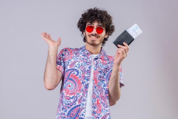 Glimlachende jonge knappe krullende reizigersmens die zonnebril draagt die portefeuille en vliegtuigtickets houdt en lege hand op geïsoleerde witte muur toont