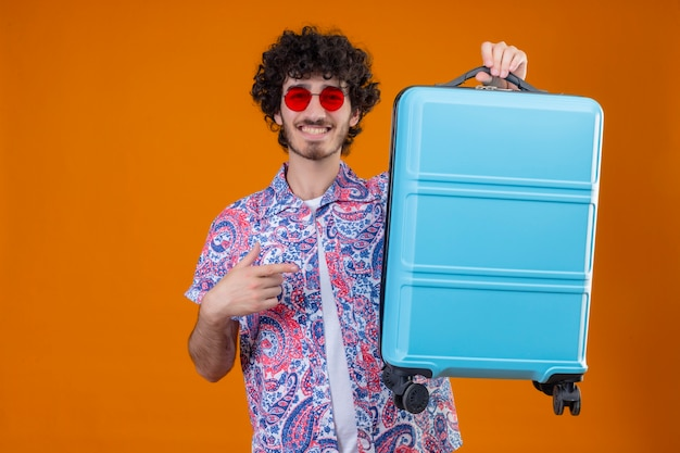 Glimlachende jonge knappe krullende reizigersmens die zonnebril draagt en koffer opheft die ernaar op geïsoleerde oranje muur met exemplaarruimte richt