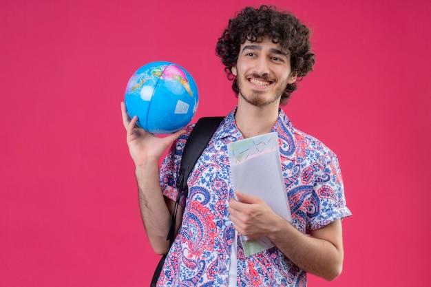 Glimlachende jonge knappe krullende reizigersmens met bol en notitieblok op geïsoleerde roze muur met exemplaarruimte