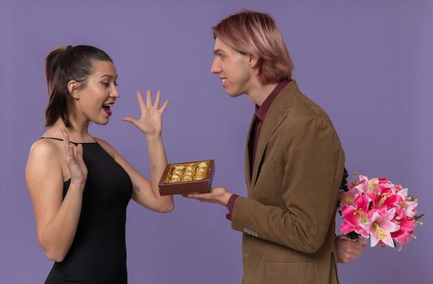 Glimlachende jonge knappe man die een boeket bloemen vasthoudt en een chocoladedoos geeft aan een opgewonden mooie jonge vrouw