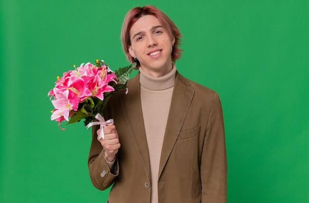 Glimlachende jonge knappe man die een boeket bloemen vasthoudt en kijkt