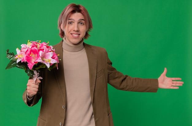 Glimlachende jonge knappe man die een boeket bloemen vasthoudt en met zijn hand naar de zijkant wijst