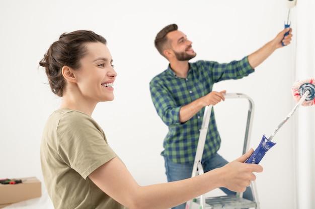 Glimlachende jonge knappe man die muur schildert met verfroller terwijl hij kamer verbouwt met vrouw