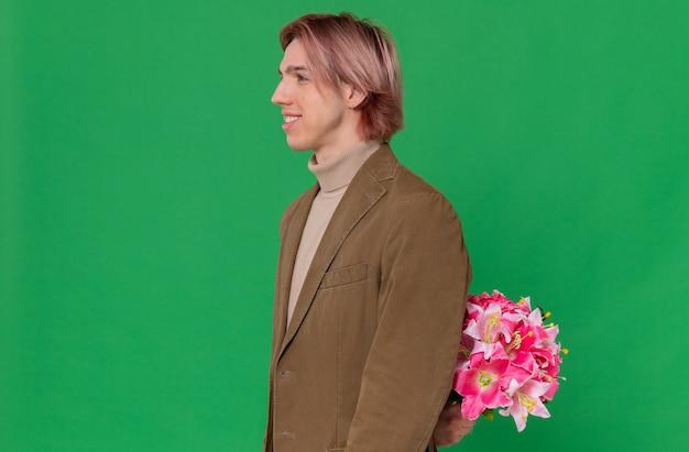 Glimlachende jonge knappe man die zijwaarts staat en een boeket bloemen achter zijn rug houdt