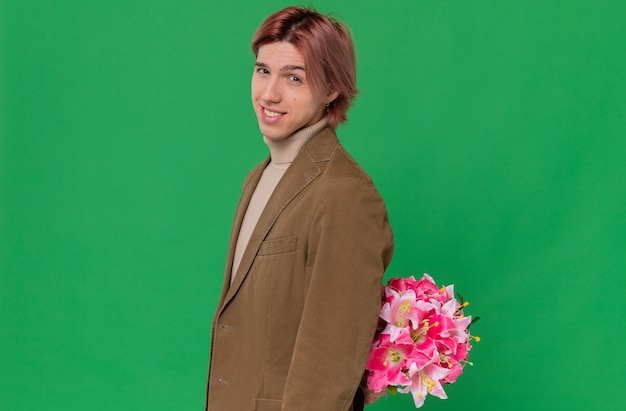 Glimlachende jonge knappe man die zijwaarts staat en een boeket bloemen achter zijn rug vasthoudt terwijl hij kijkt