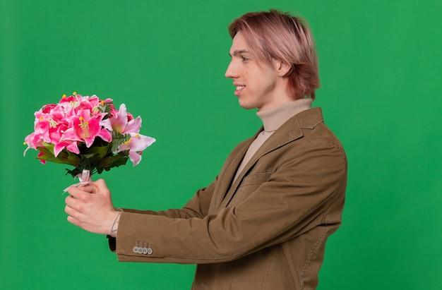 Glimlachende jonge knappe man die zijwaarts staat en een boeket bloemen vasthoudt