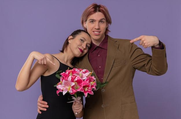 Glimlachende jonge knappe man en tevreden mooie jonge vrouw wijzend op boeket bloemen
