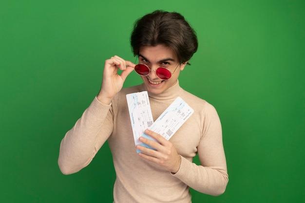 Glimlachende jonge knappe man met een bril met kaartjes en een bril geïsoleerd op een groene muur