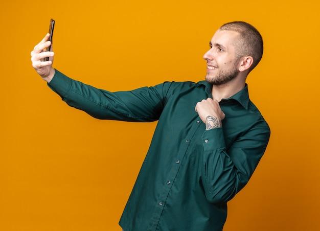 Glimlachende jonge knappe man met een groen shirt maakt een selfie