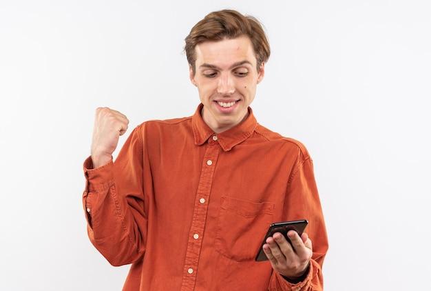 Glimlachende jonge knappe man met een rood shirt die vasthoudt en naar een telefoon kijkt met een ja-gebaar dat op een witte muur wordt geïsoleerd
